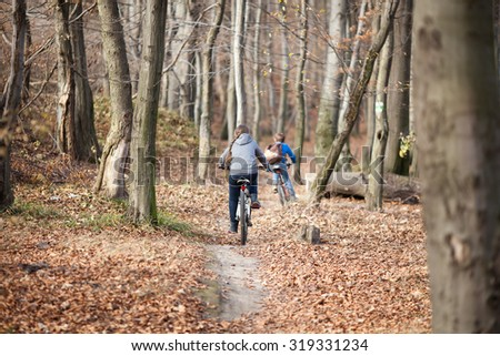 Two children on bicycles in autumn forest - stock photo