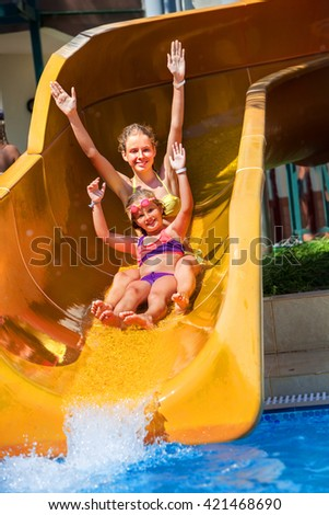 Two children on water slide at aquapark and hand up. Summer holiday. There are two water slides in aqua park. Children activities lifestyle. Outdoor. - stock photo