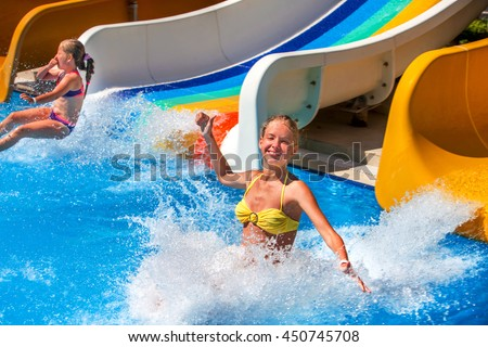 Two children on water slide at aquapark and thumb up. Summer holiday. There are two water slides in aqua park. Outdoor. Water children holiday. - stock photo