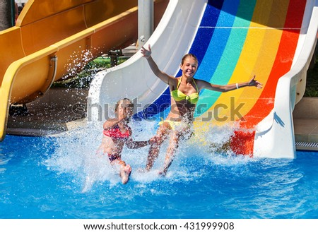 Two children on water slide at aquapark show thumb up. Summer swimming holiday. There are two water slides in aqua park. Swimming outdoor. - stock photo