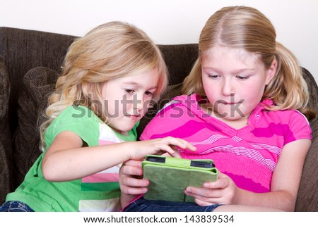 Two children or sisters using tablet, sitting on couch - stock photo
