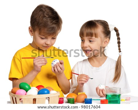 Two children painting Easter eggs isolated on white background