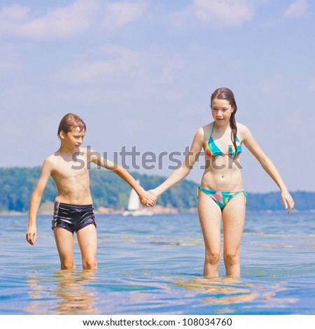 Two children playing in water, girl and boy holding hands