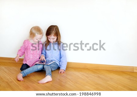 Two children playing on a digital tablet at home