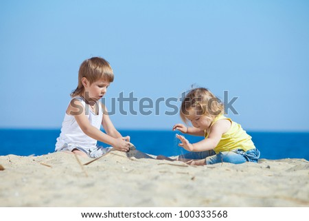 two children playing on beach - stock photo