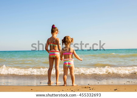 Two children playing on the beach and holding hands. Happy family vacation concept
