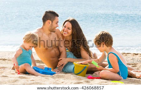 Two children playing on the beach with sand next to young parents