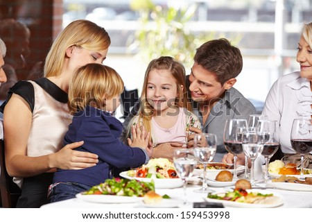 Two children playing together in a restaurant during family visit - stock photo