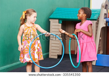 Two children playing together with hula hoops in preschool - stock photo