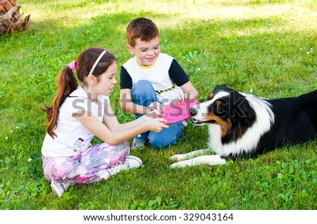Two children playing with a dog - stock photo