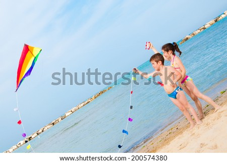 Two children playing with a kite on the beach - stock photo