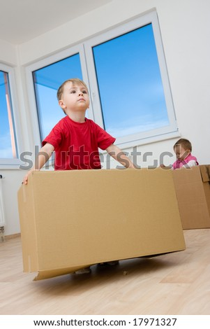 Two children playing with cardboard boxes in a room.
