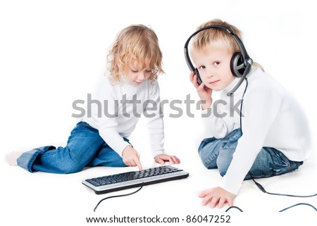 two children playing with computer on floor isolated on white background - stock photo