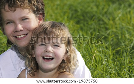 two children portrait smiling on green grass