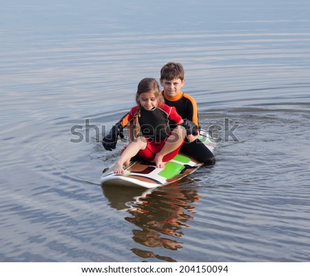 Two children practicing moving on surfboard - stock photo