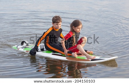 Two children practicing moving on surfboard