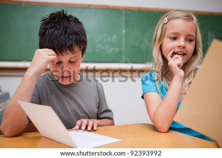 Two children reading in a classroom - stock photo