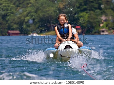 Two children riding a float being splashed by the water. - stock photo