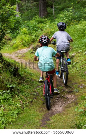 two children running bike in a forest