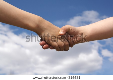 Two children shake hands as a gesture of friendship.