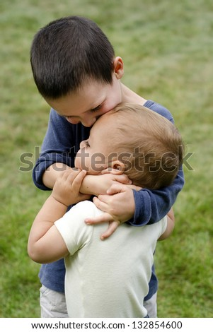 Two children, siblings, small boys, playing together outdoors; the older brother is holding the younger child around his neck, hugging and kissing him. - stock photo