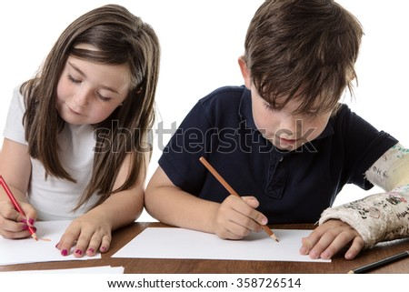 Two children sitting next to each other drawing