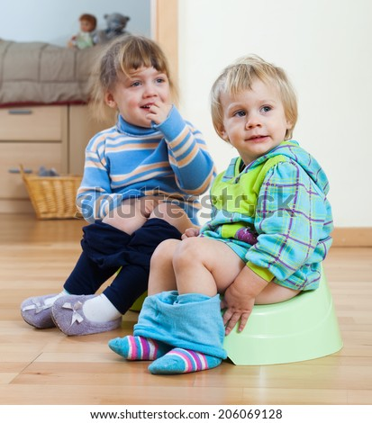 Two children sitting on bedpans in home interior - stock photo