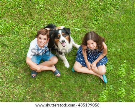Two children sitting on grass with a dog