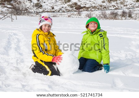 Two children sitting on snow and making snowman