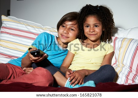 Two Children Sitting On Sofa Watching TV Together - stock photo