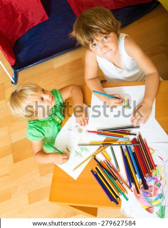 Two children sketching on paper in home interior - stock photo