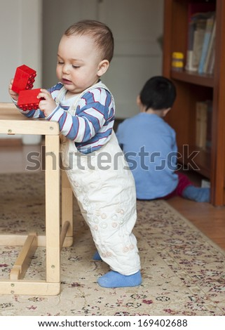 Two children, small toddler or a baby child and his older brother, playing  at home with building blocks. - stock photo