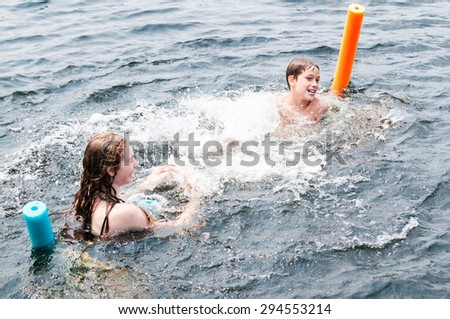 two children splashing in a lake on a summer day - stock photo
