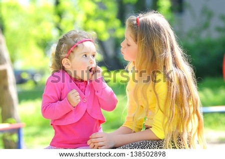 Two children talking outdoors - stock photo