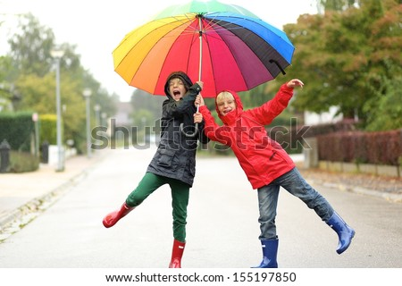 Two children, teenager twin brothers having fun outside jumping on the street under rain sharing together colorful umbrella - stock photo
