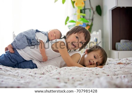 Two children, toddler and his big brother, hugging and kissing their newborn baby brother at home, few days after delivery