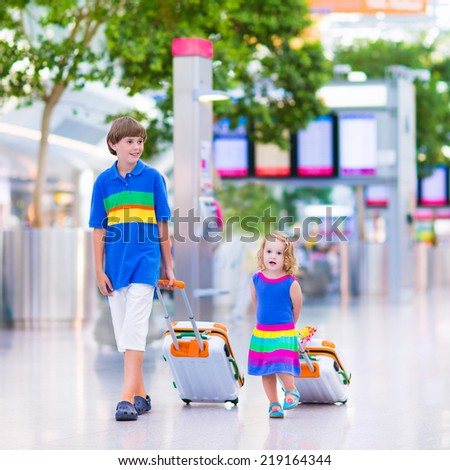 Two children traveling by airplane at Dusseldorf International airport, laughing teenager boy and a toddler girl, brother and sister holding colorful luggage ready to fly for summer beach vacation  - stock photo