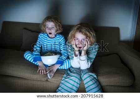 two children watching tv together shocked expressions - stock photo