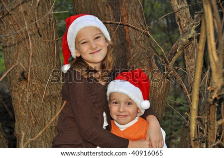 two children wearing santa hats embrace by a tree - stock photo