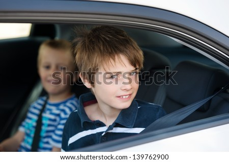 Two children wearing seatbelts in the car in a close up shot - stock photo