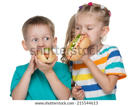 Two children with hot dogs on the white background