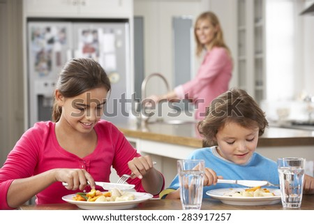 Two Children With Mother Having Meal In Kitchen Together