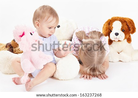 Two children with soft toys on a white background