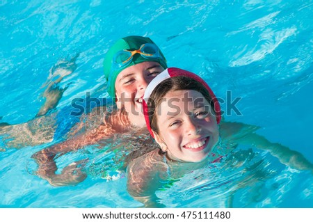 Two children with swim cap swimming in pool