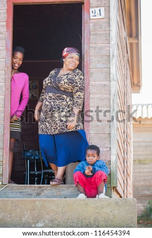 Two children with their grandmother in front of their home. - stock photo