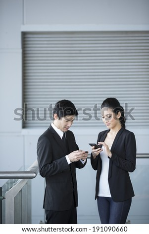 Two Chinese business colleagues talking to each other and using smartphone's. - stock photo