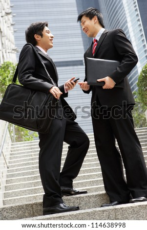 Two Chinese Businessmen Having Discussion Standing Outside Office - stock photo