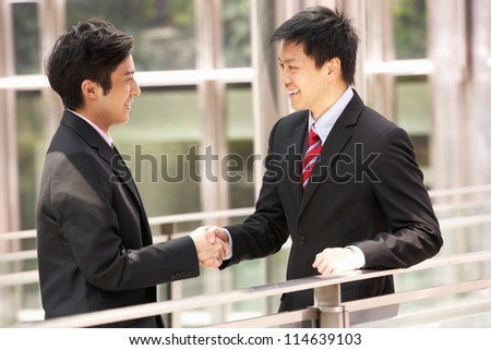 Two Chinese Businessmen Shaking Hands Outside Office