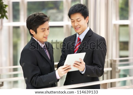 Two Chinese Businessmen Using Tablet Computer Outside Office