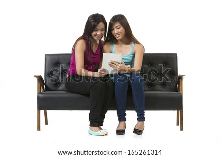 Two Chinese female friends sitting on chair using a Digital Tablet PC. Isolated on white background.